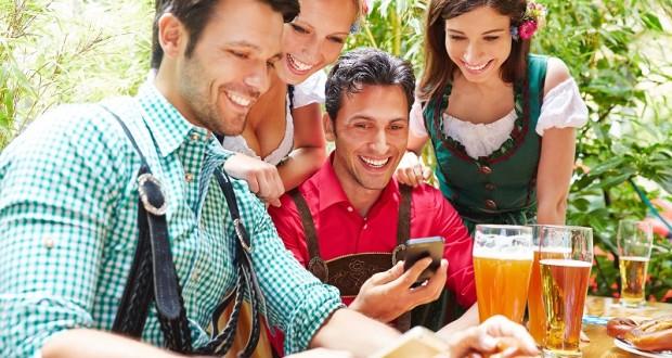 Happy friends in beer garden looking together at smartphones